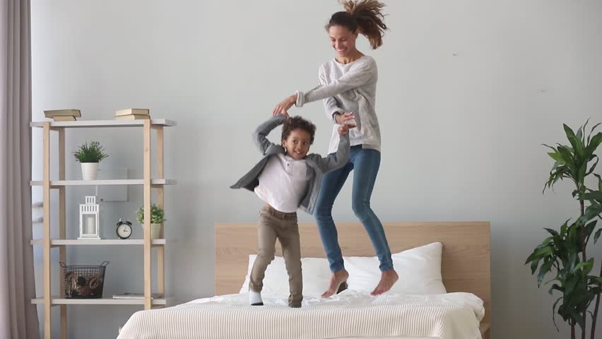 Happy family african american mixed race kid boy and caucasian mom baby sitter holding hands jumping on bed, young mother having fun laughing playing funny active game with cute child son in bedroom | Shutterstock HD Video #1027488467