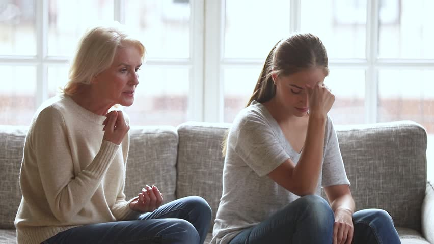 Stubborn annoyed young adult daughter turned back not listening ignoring worried stressed old senior mother arguing scolding lecturing, two different age generation women family having fight conflict