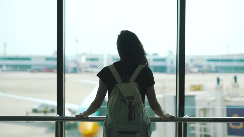 Girl standing at the window in the airport lounge. | Shutterstock HD Video #1027573337