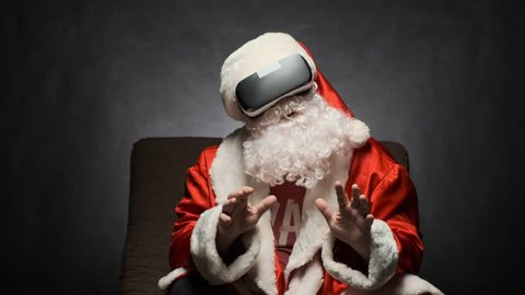 Santa Claus experiencing virtual reality while sitting in a chair on black background. Father Christmas wears VR glasses and interacts with a virtual environment.