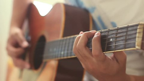 Man practicing guitar with slow motion shoot music musician classic chord acoustic free time holiday summer. Use for illustration or insert.