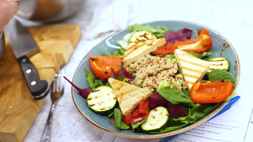 Process of cooking and decorating a vegetarian salad with tofu, kenoa and greens. Vegetable diet healthy food. Training in a culinary school, concept. Cook prepares and decorates salad in large plate