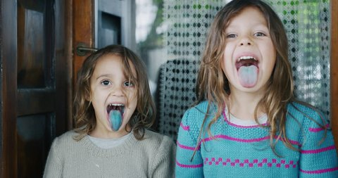 Authentic shot of two cute little girls showing coloured tongue after lollipop and smiling in camera outside her house on a sunny day.