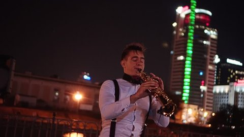 Saxophonist playing in front of the audience on the street at night. Behind him are the lights of a large building and a reservoir. Speech on the waterfront