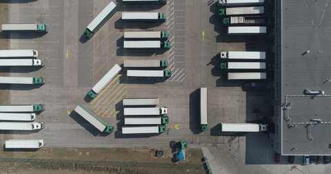 Buildings of logistics center, warehouses near the highway, view from height, a large number of trucks in the parking lot near warehouse.