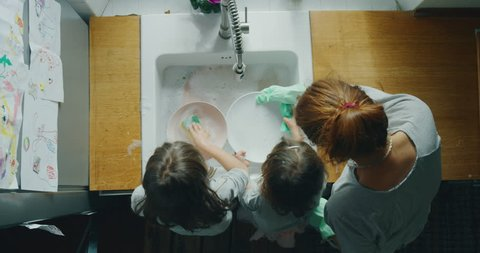 Authentic shot of little girls sisters daughters having fun to helping their mother washing plate in a kitchen on a sunny day.