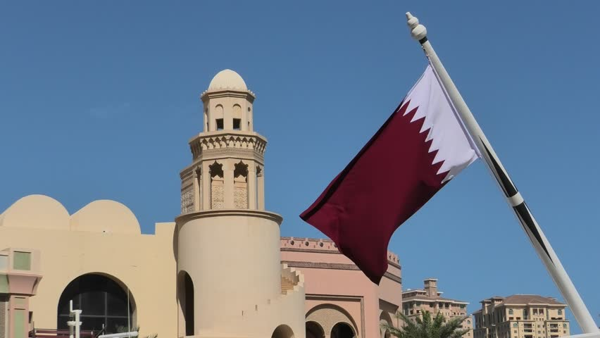Details of building with minaret in West Bay with Qatar flag in from Porto Arabia, The Pearl-Qatar's main harbor in Doha, Persian Gulf, Middle East. Famous tourist attraction.