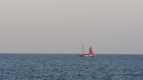 Sailboat with touristen in far away in a mediterranean sea, near town Palamos in Costa Brava