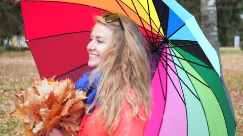 Portrait of attractive cute blonde girl in a red coat with yellow maple leaves in her hands happily walks in the autumn forest. Beautiful young woman with colourful umbrella in autumn park.