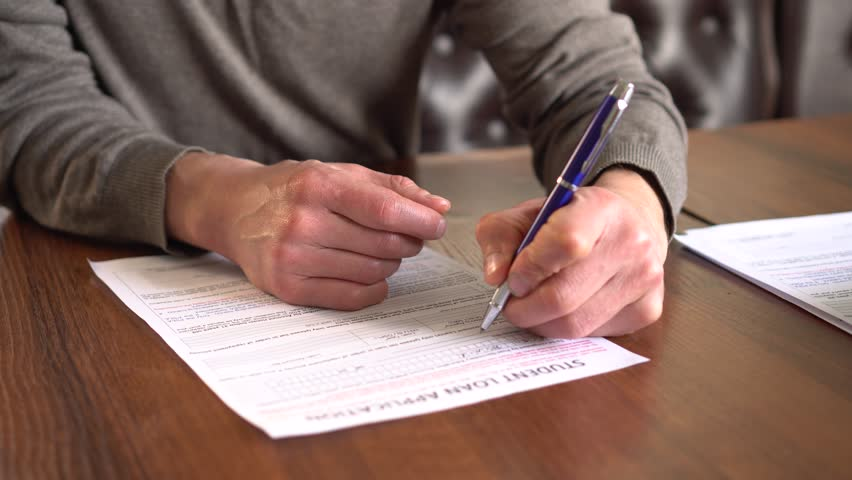 Student finance - student loans or student grants for tuition fees and living costs, extra help, Education loan repayments. A men signing loan contract