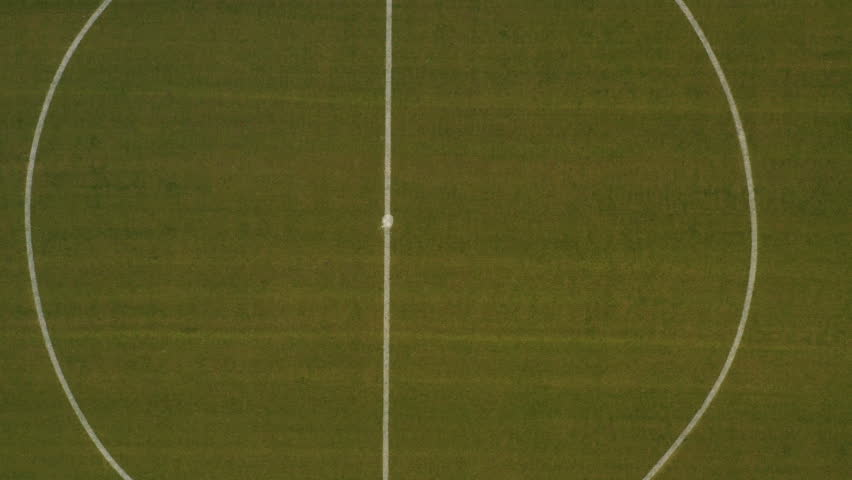 Smooth zooming out aerial footage of an empty soccer field #1027768847