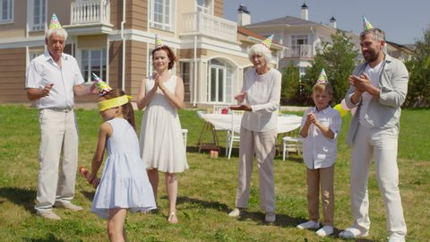 Playful little girl hitting piñata with bat while family members standing around and clapping hands at birthday celebration outdoors on summer day