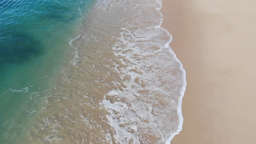 Aerial view waves break on white sand beach at sunset. Sea waves on the beautiful beach aerial view drone 4k shot. | Shutterstock HD Video #1027816757
