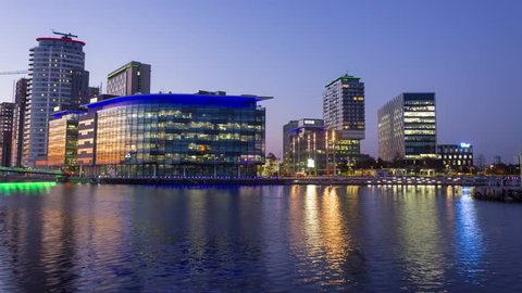 Timelapse overlooking Salford MediaCity Manchester BBC buildings at sunset day to night.