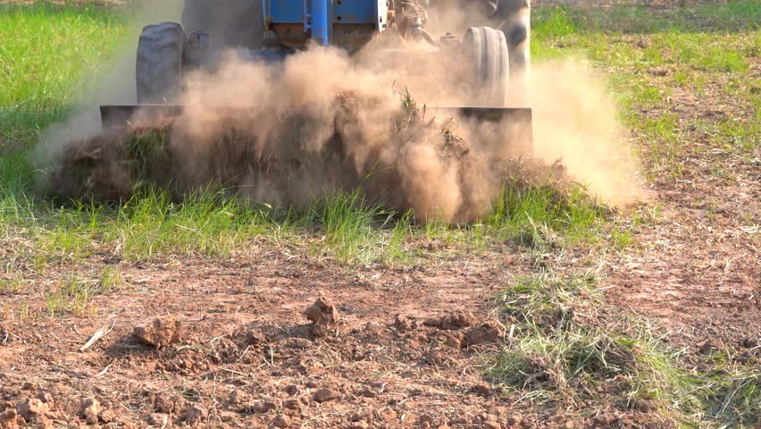 Slow motion tractor working on farmland agriculture, tractor plowing grass and soil in field land to planting rice or other plants in season, it is preparation area on pasture by vehicle in rural