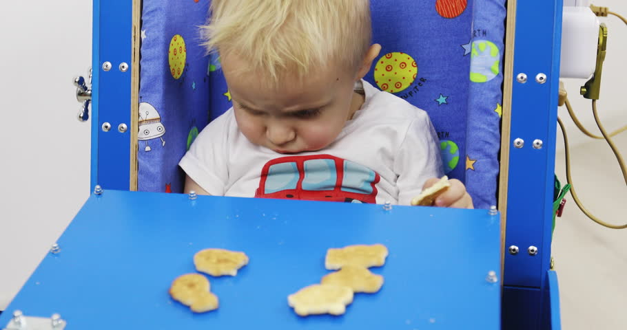 A baby's car with a table. The child eats cookies and sits in the toy. Educational toy Montessori. Fine motor skills. Sensory sensitivity.   Shutterstock HD Video #1027889987