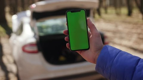 Los Angeles, California 15/03/2019 EDITORIAL: Close up hand of man using vertically smartphone blank screen and blur of his broken car parked in woods. Contacting car technician or need help concept