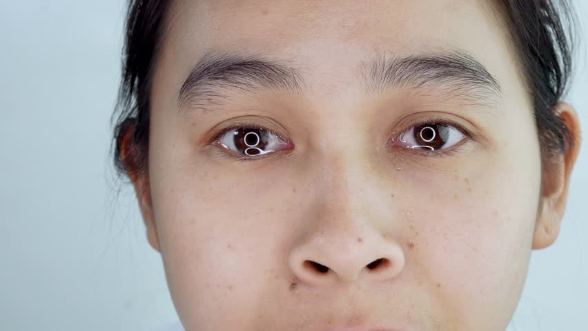 Shot of Asian young woman crying with tear in eye close up on white background.   Shutterstock HD Video #1027928897