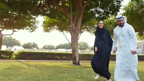 Happy muslim family spending weekend time at the park in Dubai