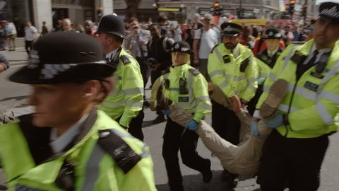 LONDON, circa 2019 - Slow motion shot of a male Extinction Rebellion demonstrator taken by police officers after being arrested in Oxford Circus, London