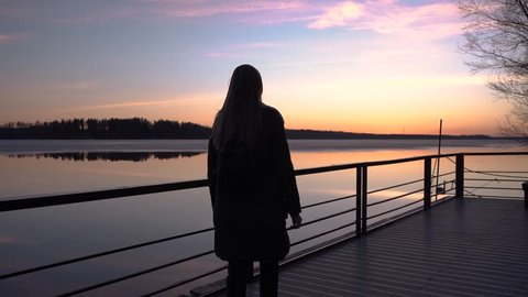 beautiful sunset, beautiful girl walking along the pier in the Harbor, and watching the sunset, the sky reflected in the water, spring ice melting on the water, vacation, out of town, camera moving, s