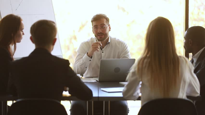 Focused businessman leader speak explain work plan at diverse group meeting sit at table, manager consult partners, boss instruct team, mentor teach interns, executive talking at corporate training