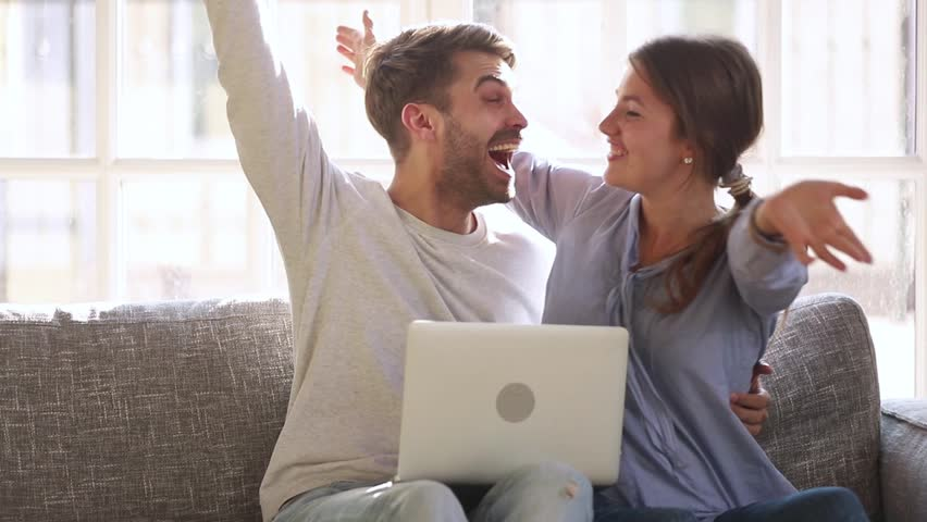 Excited happy young family couple looking at laptop computer feel winners surprised by lottery betting winning bid, celebrate good internet news embracing overjoyed by victory achievement online | Shutterstock HD Video #1028009567