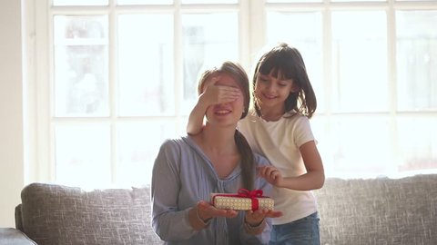 Little cute child daughter closing mom eyes congratulate happy mum with mothers day concept holding gift box, excited mommy receiving present from kid girl make surprise hugging sit on couch at home
