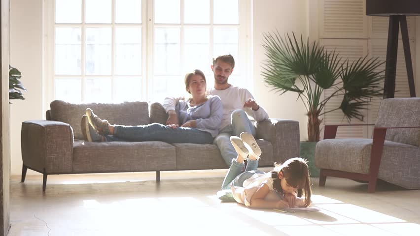 Happy family leisure at home concept, couple parents relaxing talking on sofa couch in comfort living room lit with light while little kid child daughter enjoy activity playing drawing on warm floor