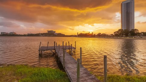 Time lapse: Beautiful and golden sunrise view with dancing clouds by a broken wooden jetty at Putrajaya, Malaysia. Pan up motion timelapse.