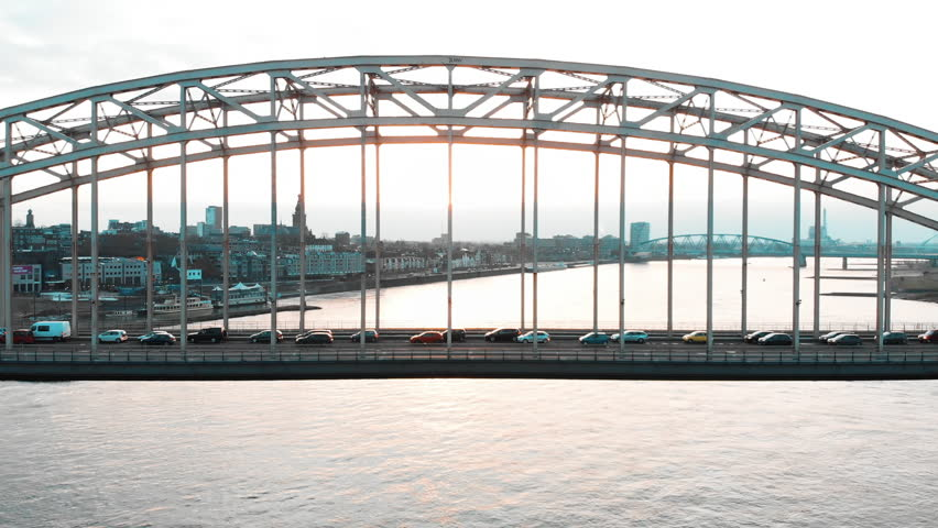 Aerial drone footage of bridge above a river with traffic. Flying backwards, dolly out. The river is 'the Waal' in the Netherlands near the city Nijmegen. #1028021897