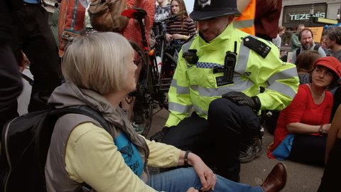 LONDON, circa 2019 - A police officer chatting to a female demonstrator of the Extinction Rebellion Group moments before being arrested in Oxford Circus, London, UK