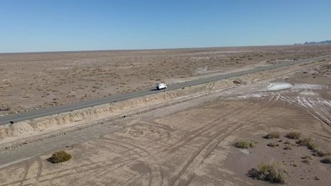 Aerial view tracking a camper truck, driving on a desert road, drone shot on a sunny day, in San Felipe, Baja, California, Mexico
