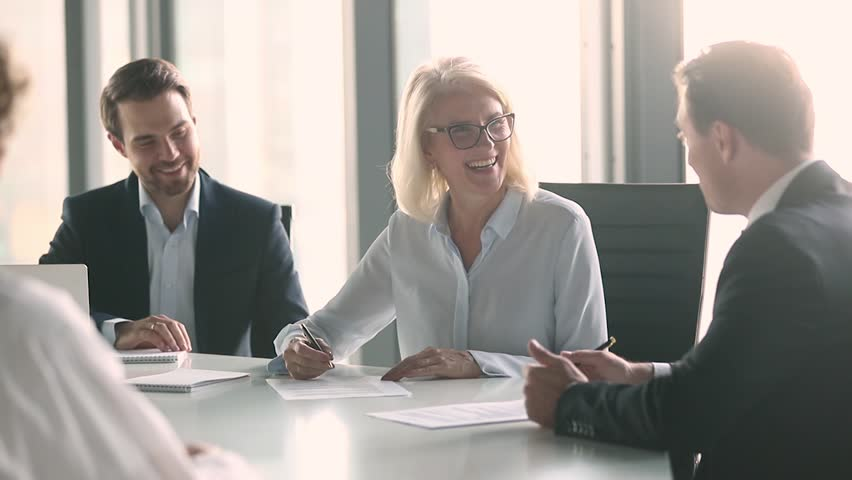 Old businesswoman and middle aged businessman partners negotiate sign contract handshake at group meeting sit at table, senior female client and male manager make agreement shake hands at negotiation
