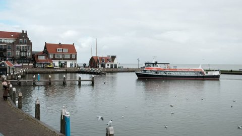 Blue orange boat sailing on the sea in Volendam with some passengers on boart. Boat enters port Volendam Netherlands 3.18.2019