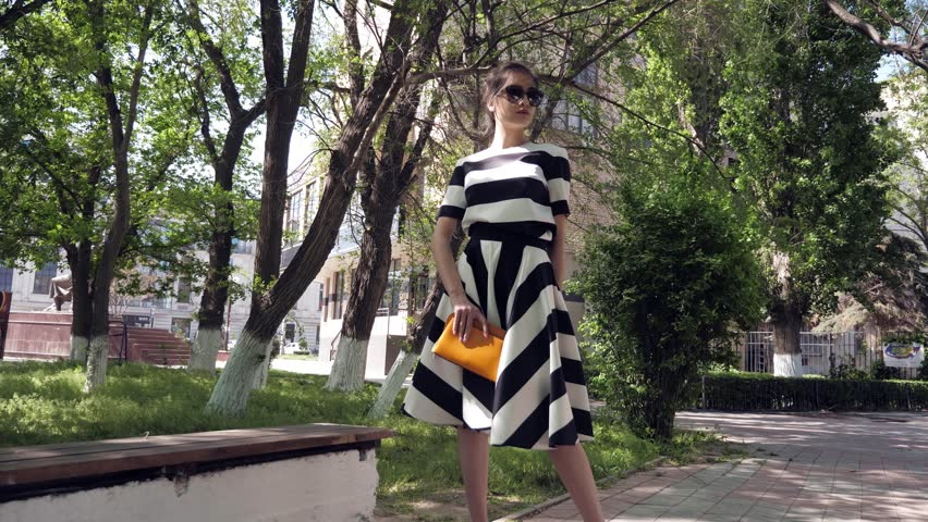 Slim pretty lady in big sunglasses black and white striped summer dress poses near bench holding mustard colored handbag | Shutterstock HD Video #1028136317