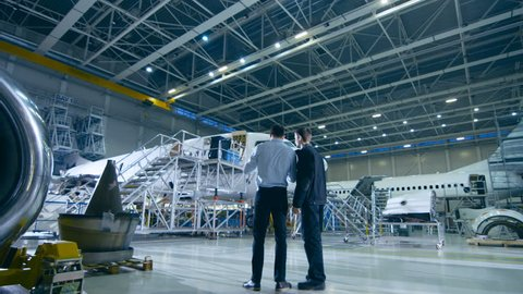 Aircraft Maintenance Mechanic and Chief Engineer Have Discussion, Consult Blueprints While Standing in a Big Airplane Development Facility. They Analyze, Inspect, Develop and Design Airplanes