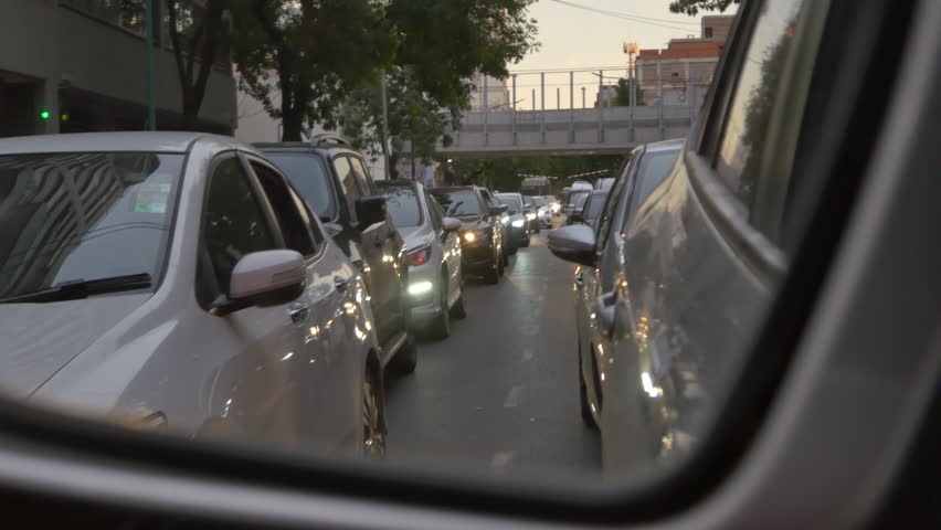 Driving a car through the city POV , hand on steering wheel close up. Mirror.Dusk, morning, sunset, early or late. Traffic jam. Many cars with light on.