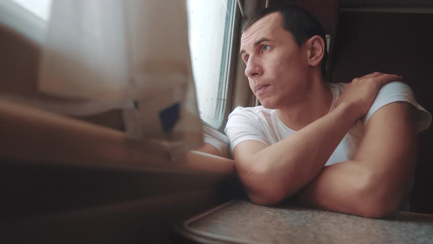 Man sad bored riding a train railway looks out the window. traveler concept train railroad journey travel. slow motion video. beautiful from lifestyle window of a moving train railway trip Russia   Shutterstock HD Video #1028162537