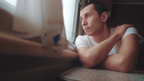 man sad bored riding a train railway looks out the window. traveler concept train railroad journey travel. slow motion video. beautiful from lifestyle window of a moving train railway trip Russia