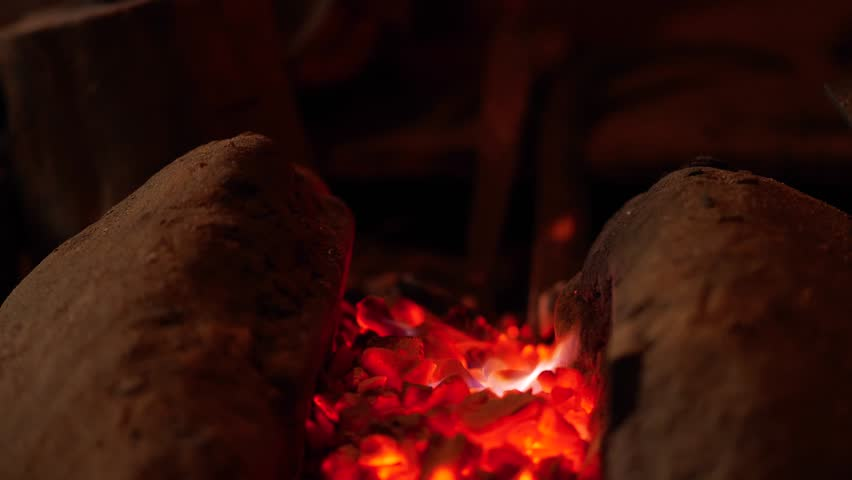 Close-up of blacksmith's hands manipulating metal piece above his forge in the smithy, selective focus. Blacksmith striking a metallic object with his hammer | Shutterstock HD Video #1028188937