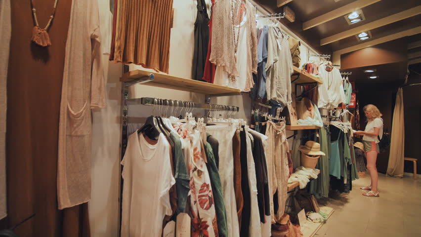 Blonde girl chooses things in the women's clothing store. | Shutterstock HD Video #1028194667