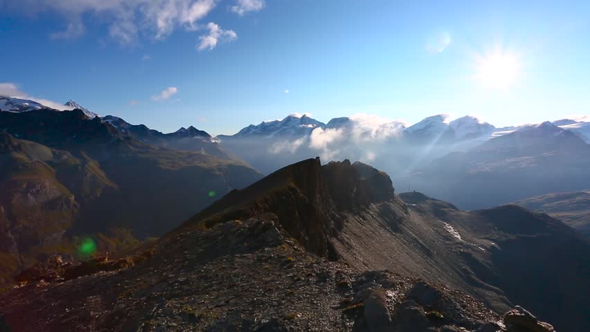 Panoramic view footage of the mountains in Matterhorn peak area during sunrise in sunny day with deep blue sky. Matterhorn (peak Cervino) in Swiss Alps. Beautiful natural landscape in the Switzerland | Shutterstock HD Video #1028210027