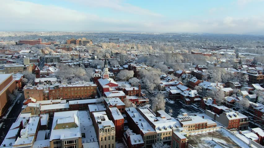 Sunlit cityscape in a cold winter morning, a small town on the East Coast USA covered in fresh snow after winter storm, sunlight breaking through clouds and illuminating the scene | Shutterstock HD Video #1028251217