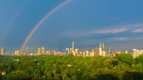 Time lapse: Silhouette of Kuala Lumpur city day view after rain with clear rainbow overlooking the city skyline from afar with lushes green trees. Federal Territory, Malaysia.