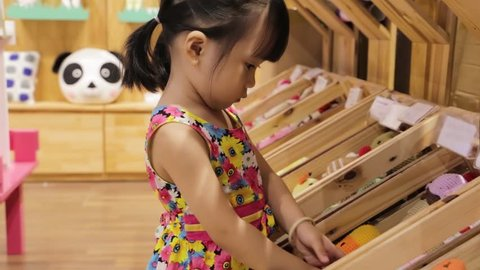 A little cute asian girl is choosing wool toys in a wooden display booth at shopping mall