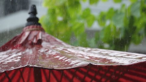 Close up of raindrops bouncing and falling down from old  red paper umbrella on a heavy rainy day,slow motion. Mulberry umbrella,art and crafts product of Thailand.
