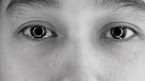 Close-up of Asian young woman's eyes crying with tear. Shot take in the studio.