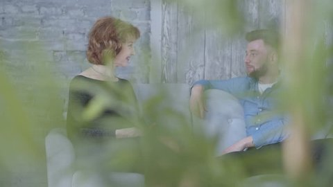 Pretty elegant mature woman talking with young man in blue shirt sitting on the sofa close up. Plant leaves cover view in the foreground. Relationship between older woman and younger man