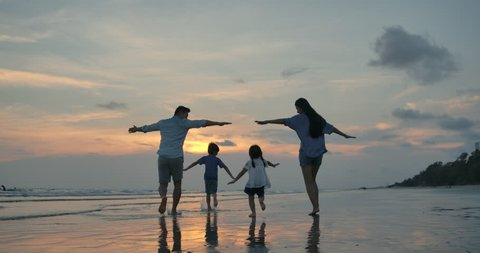Silhouetted happy asian family playing and having fun on the beach at sunset. Slow Motion. Family, Freedom and Travel concept.